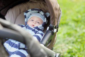 Little baby boy in stroller outdoors